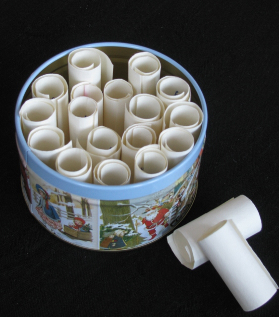 A tin filled with paper scrolls